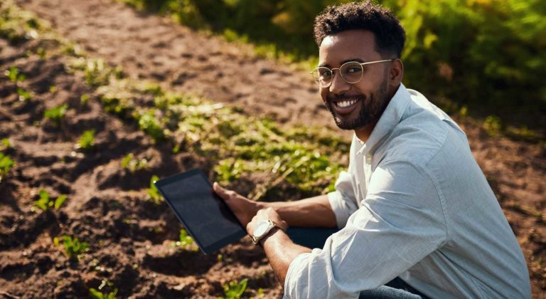 Man holding tablet while planting crops membership